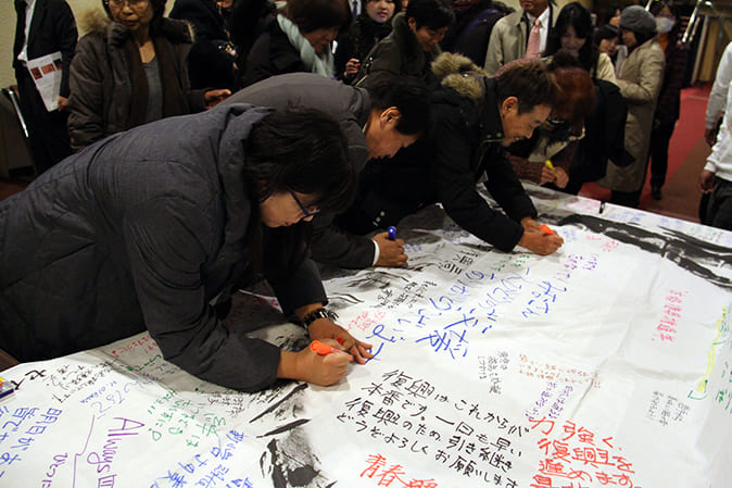 "Concert goers were given the opportunity to write messages for people in the stricken areas on ""Wa"" flags"